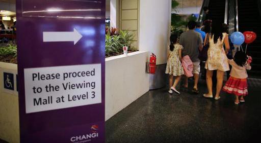 Un cartel indica la zona a la que deben dirigirse los parientes de los pasajeros del vuelo QZ8501 de AisAsia desaparecido, en el aeropuerto internacional de Changi, en Singapur, el 28 de diciembre  de 2014.