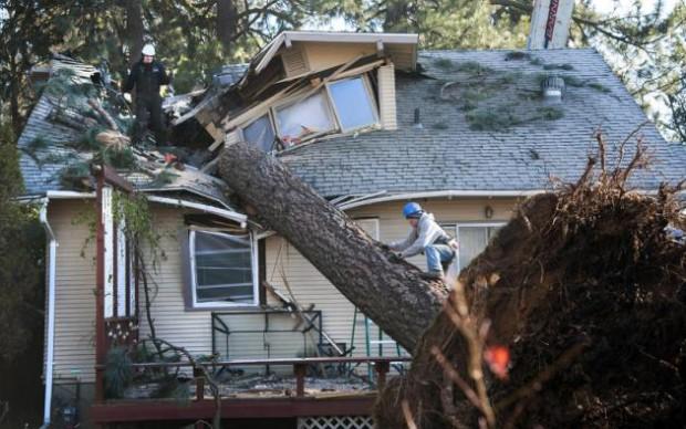 En esta imagen del 21 de noviembre de 2015, Jake Hines, a la izquierda, y Ross Rukke, de Capstone Construction, trabajan para retirar un árbol caído en Spokane, Washington, luego de que poderosas tormentas azotaran el estado dejando a decenas de miles de personas sin electricidad. (Dan Pelle/The Spokesman-Review, via AP)